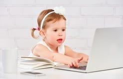 El bebé del pequeño niño trabaja en el ordenador en casa Imagen de archivo