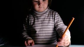El bebé dibuja en lápiz anaranjado y muestra el dibujo feliz, primer almacen de video