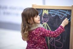El bebé dibuja tiza en la pizarra en las compras del área de los niños fotos de archivo