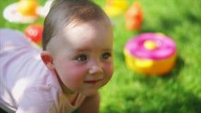 El bebé divertido y lindo se arrastra en las piernas y las manos en hierba verde en verano almacen de video