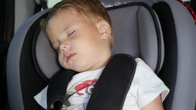 El bebé duerme en el coche de la manera Niño durmiente en la silla trasera en coche en la cámara lenta almacen de video