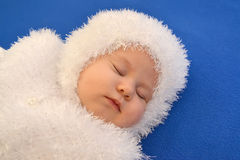 El bebé durmiente en un traje del Año Nuevo del copo de nieve en un fondo azul Fotografía de archivo