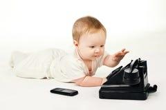El bebé elige los teléfonos Imagen de archivo