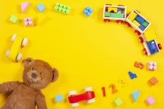 El bebé embroma el fondo de los juguetes con el oso de peluche, el tren de madera, los bloques coloridos y los ladrillos en fondo imagenes de archivo