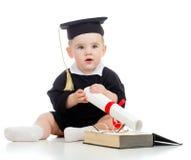 El bebé en académico arropa con el rodillo y el libro fotos de archivo libres de regalías