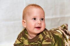 El bebé en camuflaje viste en un fondo blanco Foto de archivo libre de regalías