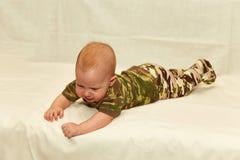 El bebé en camuflaje viste en un fondo blanco Fotos de archivo