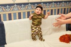 El bebé en camuflaje viste en un fondo blanco Imagenes de archivo