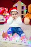 El bebé en casquillo rojo se sienta en fondo de una guirnalda de luces, los osos de peluche y las casas y los juegos del juguete fotos de archivo