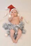 El bebé en el casquillo de Papá Noel con las decoraciones del árbol de navidad en backgroundrations ligeros encendido Foto de archivo libre de regalías
