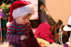 El bebé en el sombrero de Papá Noel guarda un libro Imagen de archivo libre de regalías