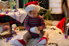 El bebé en el sombrero de Papá Noel guarda y mirando sus zapatos Fotografía de archivo