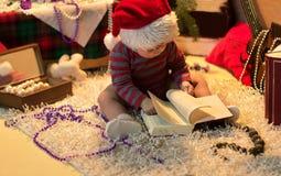 El bebé en el sombrero de Papá Noel leyó un libro Imagenes de archivo