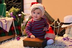 El bebé en el sombrero de Papá Noel se sienta en la alfombra y la apertura de una caja Imágenes de archivo libres de regalías