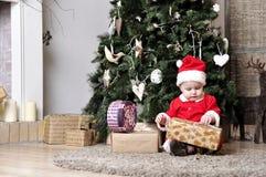 El bebé en el traje de Papá Noel se sienta cerca de adornar el árbol de navidad y el intento desempaqueta la actual caja Imagen de archivo libre de regalías