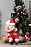 El bebé en el traje de Papá Noel se sienta con la madre en el adornamiento del árbol de navidad Foto de archivo