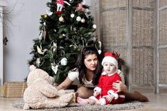 El bebé en el traje de Papá Noel se sienta con la madre en el adornamiento del árbol de navidad Imágenes de archivo libres de regalías