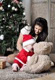 El bebé en el traje de Papá Noel se sienta con la madre en el adornamiento del árbol de navidad Fotos de archivo