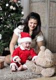El bebé en el traje de Papá Noel se sienta con la madre en el adornamiento del árbol de navidad Imagenes de archivo