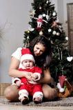 El bebé en el traje de Papá Noel se sienta con la madre en el adornamiento del árbol de navidad Foto de archivo libre de regalías
