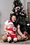 El bebé en el traje de Papá Noel se sienta con la madre en el adornamiento del árbol de navidad Fotos de archivo libres de regalías