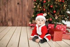 El bebé en el traje de santa con los regalos acerca al árbol de Navidad Fotografía de archivo