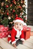 El bebé en el traje de santa con los regalos acerca al árbol de Navidad Imagen de archivo