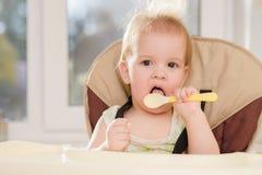 El bebé en la cocina lame una cuchara Imagen de archivo