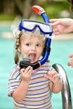 El bebé en máscara azul del zambullidor deja la piscina. Fotografía de archivo