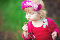 El bebé en primavera floreciente cultiva un huerto los dientes de león Fotografía de archivo libre de regalías
