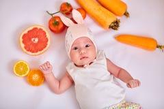 El bebé en sombrero con los oídos del conejito miente en el fondo blanco con las frutas y verduras - comida sana, zanahorias, tom imagenes de archivo