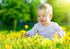 El bebé en un prado verde con amarillo florece los dientes de león en el th Imagen de archivo
