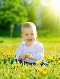 El bebé en un prado verde con amarillo florece los dientes de león en el th Fotos de archivo