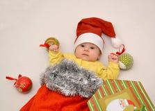 El bebé en un traje del Año Nuevo de Santa Claus con las decoraciones del árbol de navidad Fotos de archivo libres de regalías