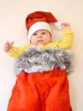 El bebé en un traje del Año Nuevo de Santa Claus en un backgroun ligero Imagenes de archivo