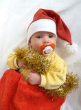 El bebé en un traje del Año Nuevo de Santa Claus en un fondo blanco Fotografía de archivo