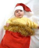 El bebé en un traje del Año Nuevo de Santa Claus en un fondo blanco Foto de archivo