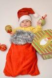 El bebé en un traje del ` s del Año Nuevo de Santa Claus con las decoraciones del árbol de navidad Foto de archivo libre de regalías
