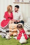 El bebé en un vestido rojo se sienta en una manta con los juguetes de la felpa en el cuarto contra la perspectiva de sus padres e foto de archivo