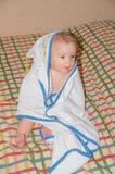 El bebé en una toalla en la cama Fotografía de archivo libre de regalías