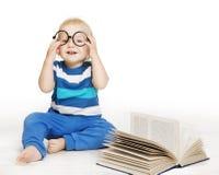 El bebé en vidrios leyó el libro, niños tempranos educación, niño en blanco fotografía de archivo