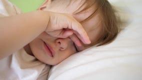 El bebé encantador se cae dormido en la cama blanca en su cama en sitio en casa concepto de niño durmiente el niño quiere dormir  imágenes de archivo libres de regalías