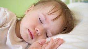El bebé encantador se cae dormido en la cama blanca en su cama en sitio en casa concepto de niño durmiente el niño quiere dormir  foto de archivo