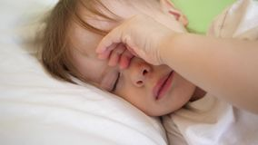 El bebé encantador se cae dormido en la cama blanca en su cama en sitio en casa concepto de niño durmiente el niño quiere dormir  metrajes
