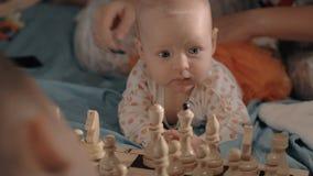 El bebé es curioso sobre ajedrez almacen de metraje de vídeo
