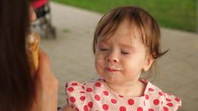 El bebé está comiendo el helado con la galleta metrajes