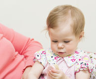 El bebé está considerando un cepillo para el pelo. Imagen de archivo