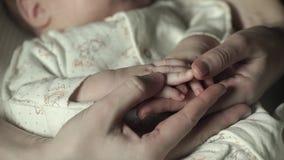 El bebé está durmiendo en el pesebre La mamá está tocando sus fingeres almacen de video