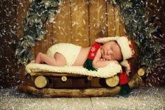 El bebé está durmiendo en trineos de madera ` S Eve del Año Nuevo Imagen de archivo