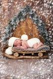 El bebé está durmiendo en trineos de madera ` S Eve del Año Nuevo Foto de archivo libre de regalías